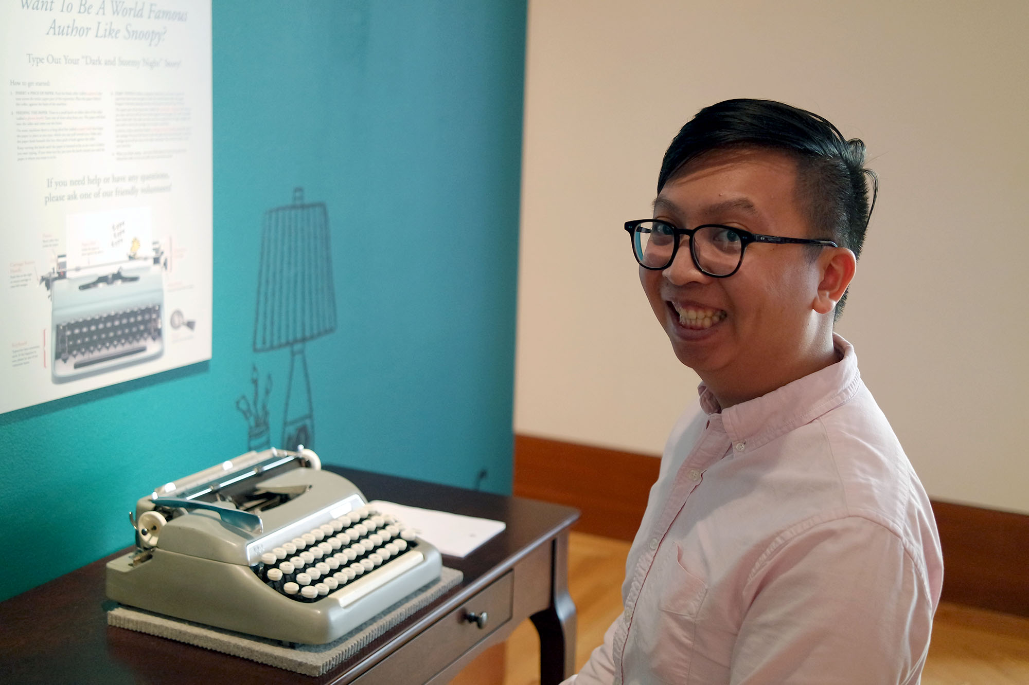 Picture of an Asian man sitting at a typewriter.